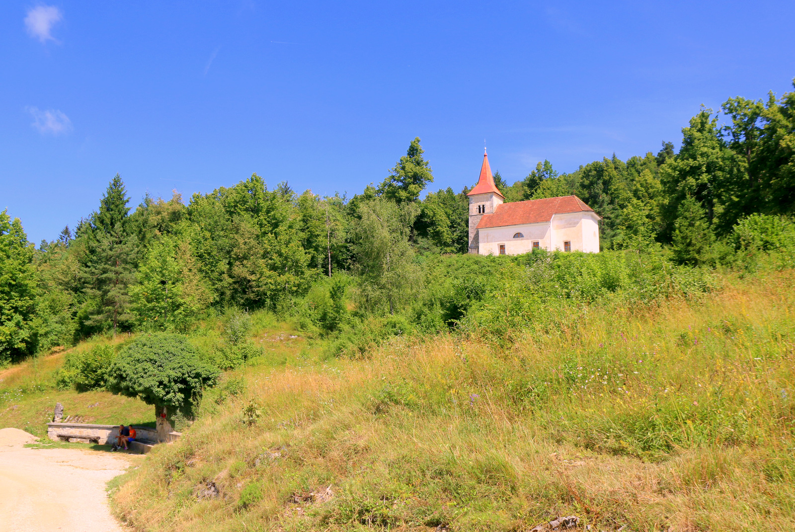 Studenec, kapelica Lurške Matere Božje in v ozadju cerkev Sv. Lenarta v vasi Dobec